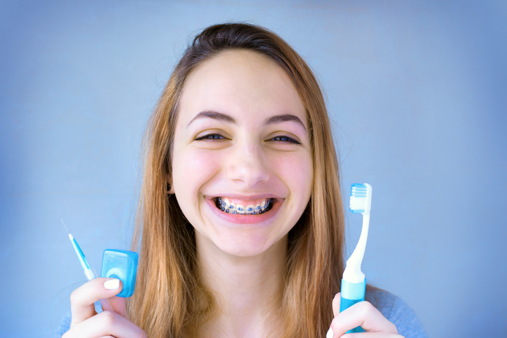 Girl with braces holding toothbrush and flush
